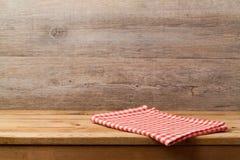 Tom trädäcktabell med den kontrollerade röda bordduken över träväggbakgrund för produktmontage royaltyfri fotografi