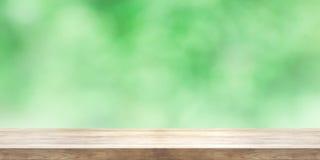 Tom trätabellöverkant med suddig grön naturlig abstrakt backg Arkivbild