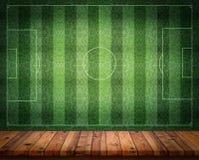 Tom trätabell eller räknare med backgroun för vägg för fotbollfält arkivfoton