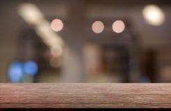 Tom trätabell framme av abstrakt suddig bakgrund av den restaurang-, kafé- och coffee shopinre kan användas för skärm arkivbild