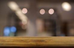 Tom trätabell framme av abstrakt suddig bakgrund av den restaurang-, kafé- och coffee shopinre kan användas för skärm royaltyfria bilder