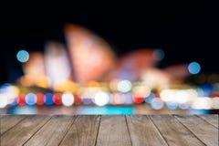 Tom trätabell framme av suddiga unidentifiable suddiga Sydney Opera House i bakgrund royaltyfri bild