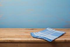 Tom trätabell med den kontrollerade blåa bordduken över den lantliga målade väggen Royaltyfri Fotografi