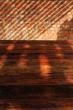 Tom trätabell med skugga för tegelstenvägg och solljus Arkivbilder