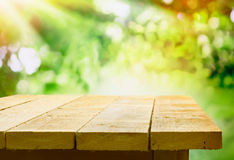 Tom trätabell med trädgårds- bokeh