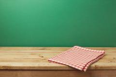 Tom trätappningtabell med den röda kontrollerade bordduken över den gröna väggen Arkivbild