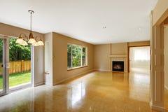 Tom vardagsrum med det skinande den marmortegelplattagolvet och spisen Royaltyfria Bilder