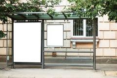 Tom vitåtlöje upp av den vertikala affischtavlan för hållplats framme av tom gatabakgrund Royaltyfri Fotografi