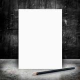Tom vit affisch och blyertspenna i ett glansig konkret golv och bla Arkivfoto