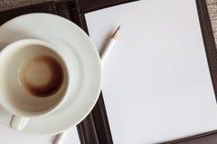 Tom vit anteckningsbok, blyertspenna och tom kaffekopp Royaltyfria Foton
