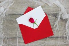 Tom vit förälskelsebokstav och rött kuvert med den enkla röda rosen Royaltyfri Foto