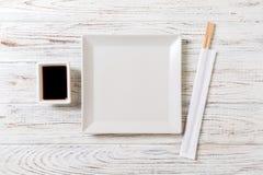Tom vit fyrkantig platta med pinnar för sushi och soya på träbakgrund B?sta sikt med kopieringsutrymme arkivfoto