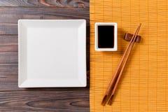 Tom vit fyrkantig platta med pinnar för sushi och soya på träbakgrund B?sta sikt med kopieringsutrymme royaltyfri fotografi