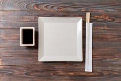 Tom vit fyrkantig platta med pinnar för sushi och soya på träbakgrund B?sta sikt med kopieringsutrymme arkivbilder
