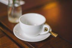 Tom vit kopp för närbild med tefatet och skeden på en tabell arkivfoto