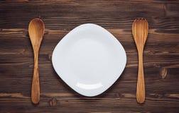 Tom vit maträtt med träskedar på mörk träbakgrund Fotografering för Bildbyråer