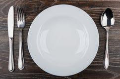Tom vit platta, kniv, gaffel och sked på tabellen Royaltyfri Bild
