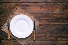 Tom vit platta med gaffeln och kniv på lantlig träbakgrund Royaltyfri Foto