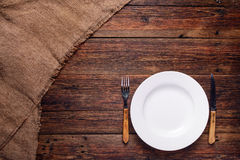 Tom vit platta med gaffeln och kniv på lantlig träbakgrund Royaltyfri Fotografi
