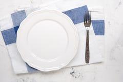 Tom vit platta och gaffel på en tabell, bästa sikt arkivbild