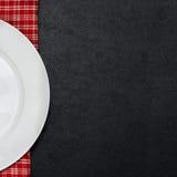 Tom vit platta på en rutig servett- och svartbakgrund royaltyfri foto
