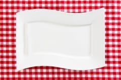 Tom vit platta på röd servett eller bordduk Top beskådar Mall för din mat- och produktskärmmontage Begreppsmat kopia arkivfoto