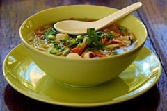 Tom yam spicy sooup. Tom yam thai seafood soup closeup on wooden background with spoon Stock Photos