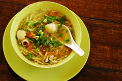 Tom yam spicy sooup. Tom yam thai seafood soup closeup on wooden background with spoon pictured from above Stock Images