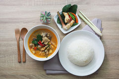 Tom yum chicken soup served with hot steamed rice. And on the brown table wooden Royalty Free Stock Images