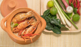 Tom Yum Goong in a clay pot spicy soup traditional thai food cuisine in Thailand on mat wicker background,Tom Yum Kung,Thai Food Stock Photography