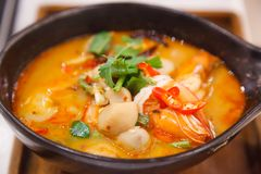 Tom Yum Goong Tom Yum Kung, Traditional Thai Sour and Spicy Tiger Prawn Soup on wooden tray, famous seafood shrimp or prawn dish stock photo