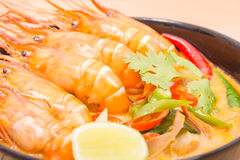 Tom Yum Goong, Thai hot spicy soup shrimp on Black Cup. With wooden table, Thailand Food Royalty Free Stock Images