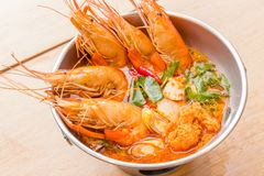 Closeup Tom Yum Goong. Tom Yum Goong Thai hot spicy soup shrimp with lemon grass,lemon,galangal and chilli on wooden background Thailand Food Royalty Free Stock Image