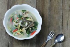 Tom Yum Grouper Fish Spicy Soup do alimento tailand?s em uma bacia no assoalho de madeira imagens de stock