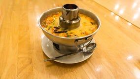 Tom Yum Koong soup pot. Famous Thai Soup recipe; Tom Yum Koong Soup in a hot pot served on a wooden table Stock Image