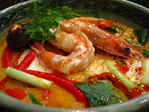 Tom Yum Kung Nam Khon. Creamy Thai soup with prawns and mushroom garnished with coriander leaves and served with lime wedges. Tom Yum Kung Nam Khon is probable royalty free stock photo