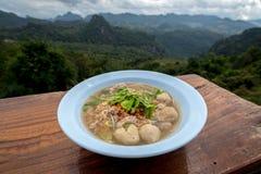 Tom Yum Noodle tailandês com carne de porco e almôndega em uma bacia na tabela de madeira pelo Mountain View atrás foto de stock