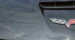 Toma panorámica a Corbeta que compite con el logotipo en el cuerpo de un coche deportivo almacen de metraje de vídeo