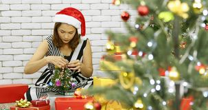 Toma panorámica del árbol de navidad adornado mujer asiática almacen de metraje de vídeo