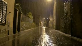Toma panorámica tirada: Lluvia fuerte de la noche en la calle principal del país