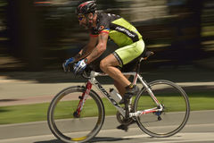 Toma panorámica de una bicicleta del montar a caballo del ciclista en un día soleado, compitiendo para el evento de Grand Prix de Fotos de archivo libres de regalías