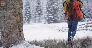Toma tur?stica del primer abajo de su bolso y comienzo anaranjados que caminan a trav?s del campo nevoso a su destino siguiente metrajes