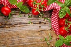 Tomaat en kruiden op hout Stock Afbeelding