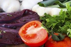 Tomaat en ongekookte lever met kruiden en kruiden Stock Afbeeldingen