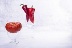 Tomaat en Spaanse pepers in de glazen op witte achtergrond Royalty-vrije Stock Fotografie