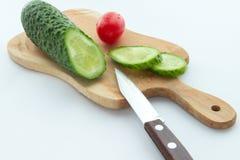 Tomaat, gesneden komkommer en een mes op scherpe raad Royalty-vrije Stock Foto's