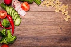 Tomaat, radijs, komkommer, broccoli, ui, Spaanse peper, deegwaren, macaroni op een houten oppervlakte regeling van gesneden groen Stock Foto's