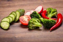 Tomaat, radijs, komkommer en broccoli, Spaanse peper op een houten oppervlakte regeling van gesneden groenten Stock Foto