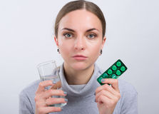 Tomada atrativa da menina comprimidos com água no fundo claro Fotografia de Stock Royalty Free