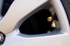 A tomada da liga para adiciona o vento no pneu Imagem de Stock